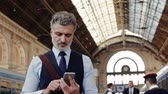 cestující : Mature businessman with smartphone on a train station. Dostupné videozáznamy