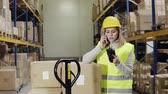 cardboard : Woman warehouse worker with smartphone.