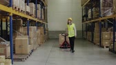 cardboard : Woman warehouse worker with hand forklift truck. Stock Footage