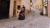 pavimentação : Senior father in wheelchair and young son on a walk.