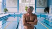nadador : Senior man in an indoor swimming pool.