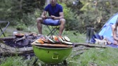 grelhar : Teenagers camping and cooking on barbecue grill.