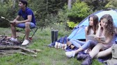 teenage girl : Teenagers camping, cooking meat on barbecue grill.