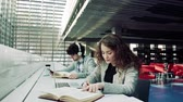 causal : Young students with laptop and headphones in a library. Stock Footage