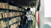 causal : Young male student walking in a library. Stock Footage