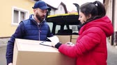 штрих код : Woman receiving parcel from delivery man at the door. Стоковые видеозаписи
