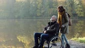 cadeira de rodas : Senior couple with wheelchair in autumn nature.