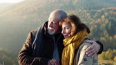 Senior couple on a walk in an autumn nature. Stok Video