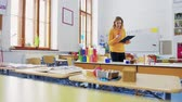 репетитор : A young woman teacher in the classroom at school.