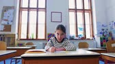 içeriye : A small girl at the desk at school, writing. Stok Video