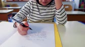 A small girl at the desk at school, writing. Stok Video