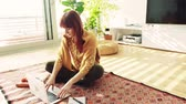 arquivos : Young woman with laptop at home, sitting on the floor and working.