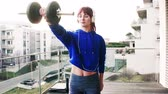 blok mieszkalny : Young fitness woman doing exercise on a balcony at home. Wideo
