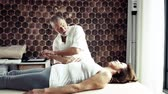 fizjoterapia : Senior physiotherapist working with a female patient.