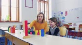 номер : A small girl with teacher learning at school.