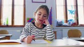 kurum : A small girl at the desk at school, writing. Stok Video