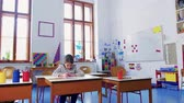 eğitmek : A small girl at the desk at school, writing. Stok Video