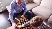 vnuk : Senior grandfather with a grandson playing chess at home. Dostupné videozáznamy