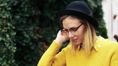 sweater : Young woman with black hat and glasses in sunny spring town.