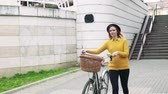 arranque : Young woman with bicycle in sunny spring town. Stock Footage