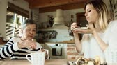 mug : Elderly grandmother with an adult granddaughter eating biscuits at home.