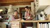 kitchen counter : An elderly grandmother with an adult granddaughter at home, baking.