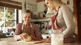 внучка : An elderly grandmother with an adult granddaughter at home, baking.