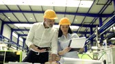 шлем : Industrial man and woman engineers with clipboard in a factory, working.