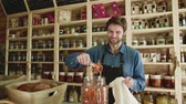 living environment : A young man shop assistant working in a zero-waste store or shop. Slow motion. Stock Footage