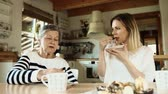 bolinhos : Elderly grandmother with an adult granddaughter eating biscuits at home.