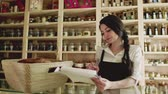 azaltmak : A young woman shop assistant working in a zero-waste store or shop.