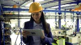 cabelos longos : An industrial woman engineer in a factory standing with tablet, working.