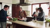 tempero : Senior couple cooking dinner together with friends at home. Stock Footage