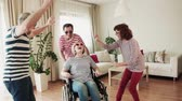 em forma de : Two senior couples with wheelchair having fun at the party at home.