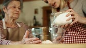 внучка : An elderly grandmother with an adult granddaughter putting flour in a bowl at home.