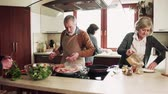 seasonings : Senior couple cooking dinner together with friends at home. Stock Footage