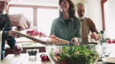 salata : Senior couple cooking dinner together with friends at home. Stok Video