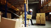 отправка : Senior male warehouse worker loading a pallet truck with boxes.