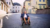 empurrando : An adult son with senior father in wheelchair on a walk in small town.
