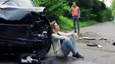 tremer : Young woman by the car after an accident and a man making a phone call.