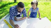 mustache : Father with a small daughter outside, planning wooden birdhouse.