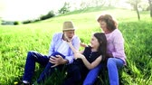 blooming : Senior couple with granddaughter sitting outside in spring nature at sunset.