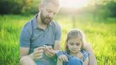 potomstvo : Father with a small daughter sitting on the grass in spring nature.