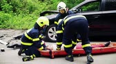 rescuing : Firefighters putting an injured woman into a plastic stretcher after a car accident.