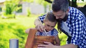 el sanatı : Father with a small daughter outside, painting wooden birdhouse. Stok Video
