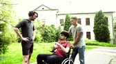 cadeira de rodas : Two teenager boys with a disabled friend in wheelchair outside in town, talking.