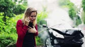 cardigã : Young frustrated woman making a phone call after a car accident.