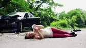 kurtarmak : Young injured woman with a broken telephone lying on the road after a car accident. Stok Video