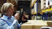 scanner : Senior woman manager and a worker working in a warehouse. Stock Footage