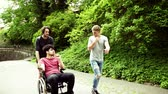 tlačení : Two teenager boys with a disabled friend in wheelchair on a walk outside in town.